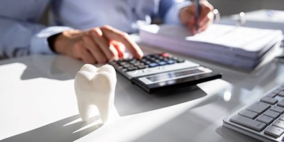 dentist calculating the cost of dental implants in Carmichael