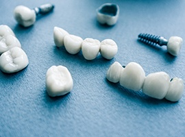 several types of dental implants in Carmichael on blue background