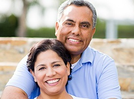 Smiling couple with dental implants in Carmichael
