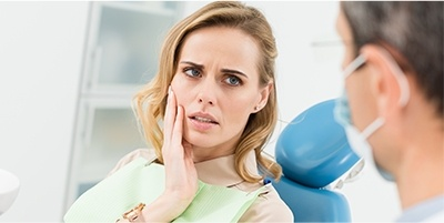 Woman in dental chair holding jaw
