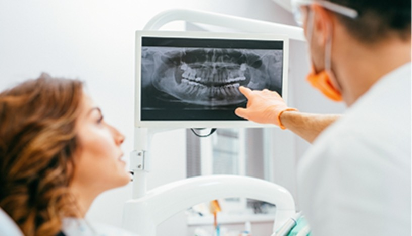 Oral surgeon and patient looking at digital x-rays