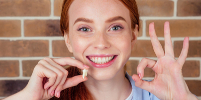 Redhead girl smiling and holding her removed wisdom tooth